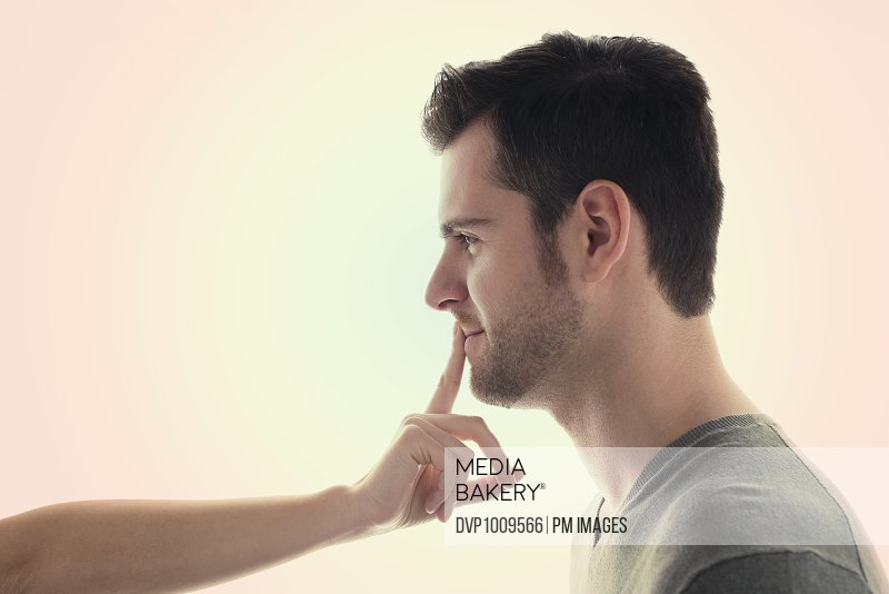 Young woman's forefinger touching lips of young man who is smiling
