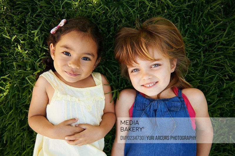 High angle portrait of two little girls lying on the grass