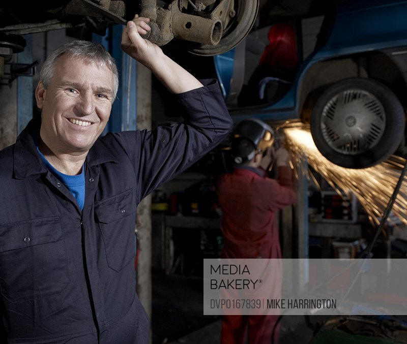 Smiling Male car mechanic in garage standing by colleague welding