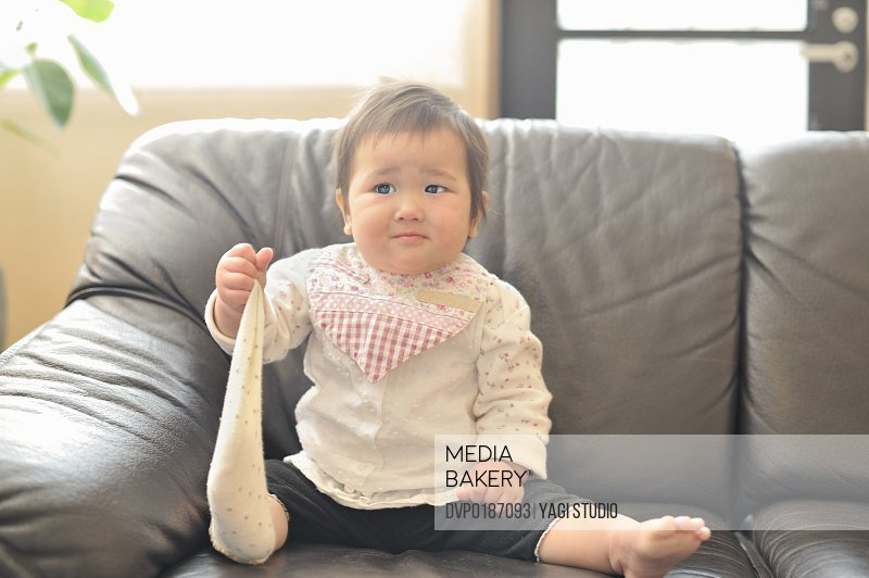 Baby girl sitting on a Sofa in a Living Room