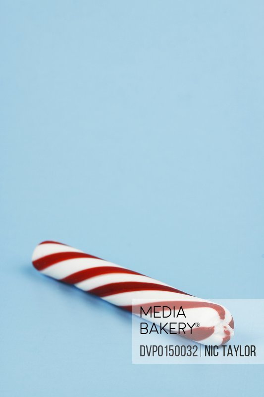 Macro image of holiday peppermint stick on a blue background. Great holiday design element.