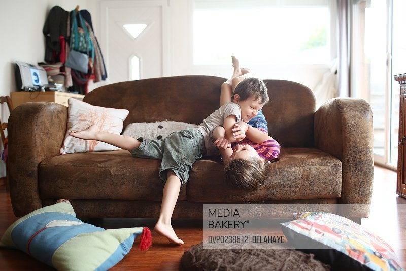 2 children playing together on a sofa