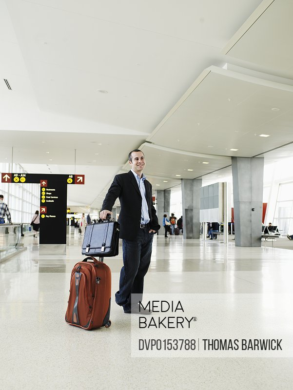 Businessman standing with luggage in airport terminal smiling
