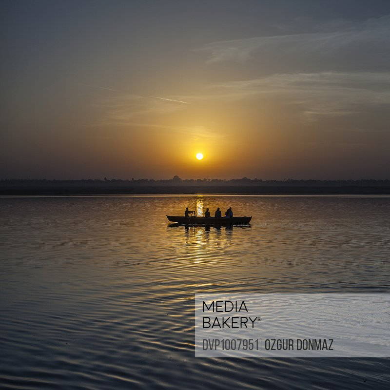 Silhouette of a row boat on the holy Ganges River at dawn