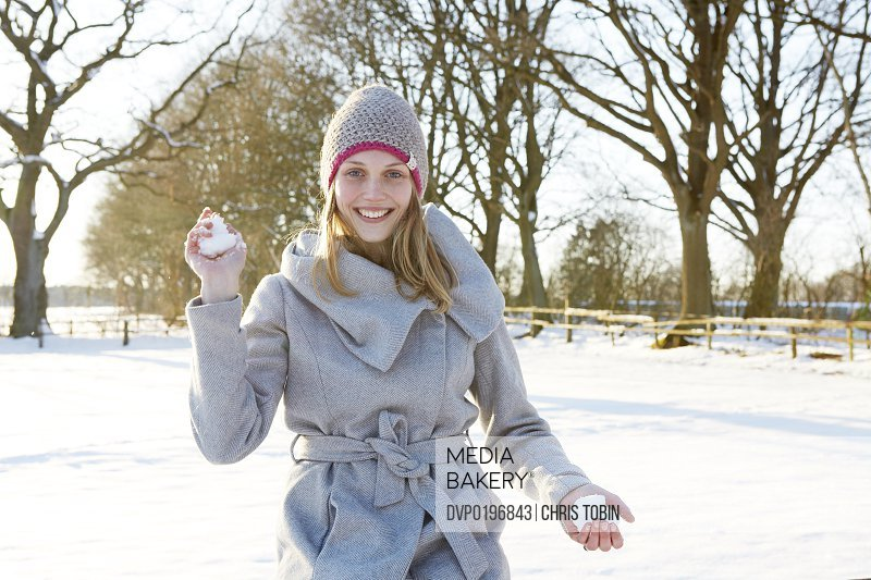 Young woman throwing snowballs