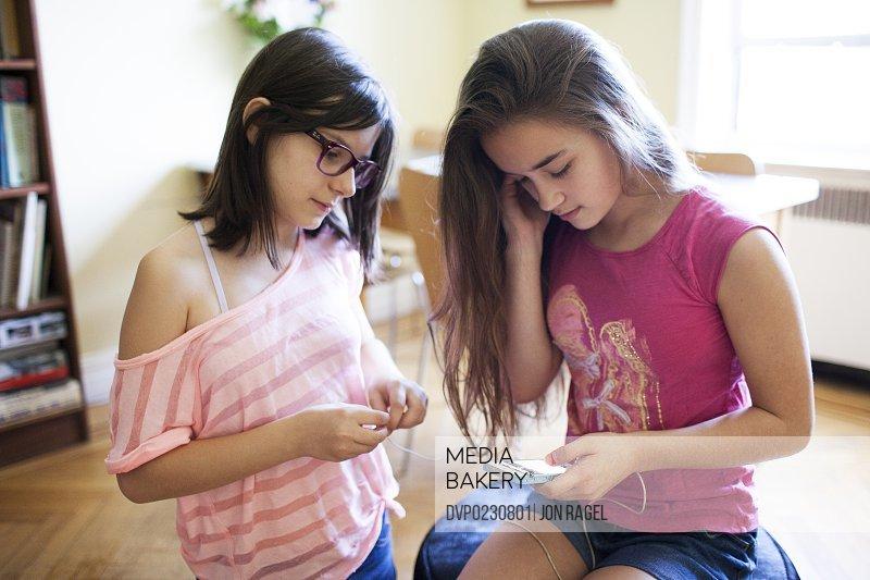 Teen girls indoors listening to music