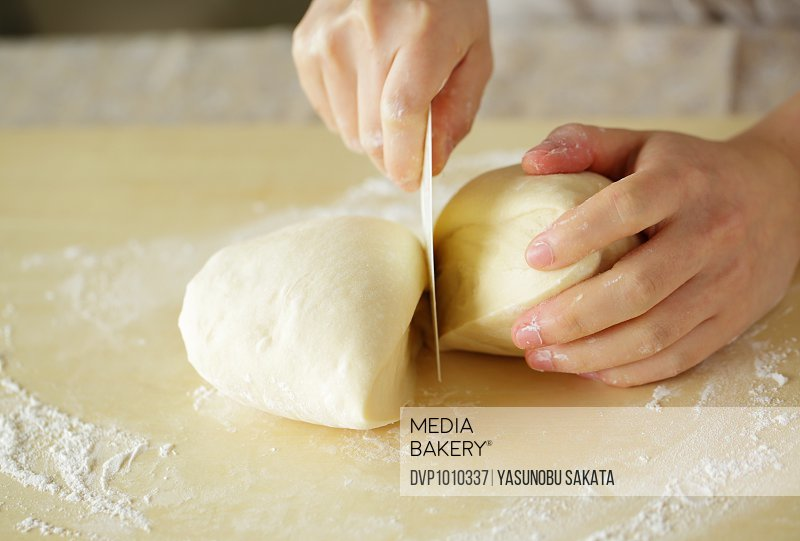 Hands of young woman cutting bread dough,close up