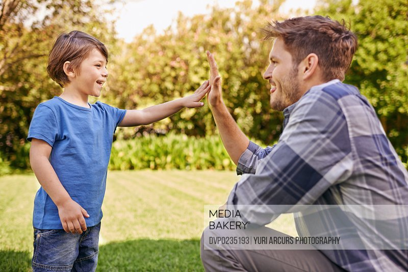 Cropped shot of a young father giving his son a high-five