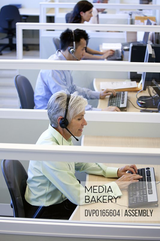 Mature female customer service representative wearing headset on the phone in a call center office