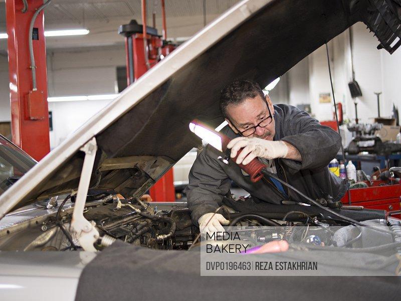 Mechanic moves light over auto engine