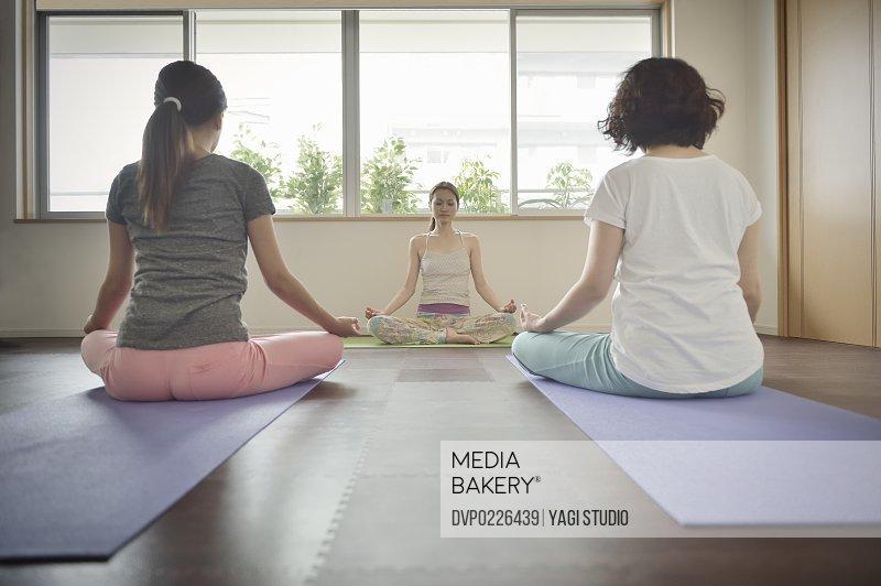 Female yoga instructor teaching yoga in room