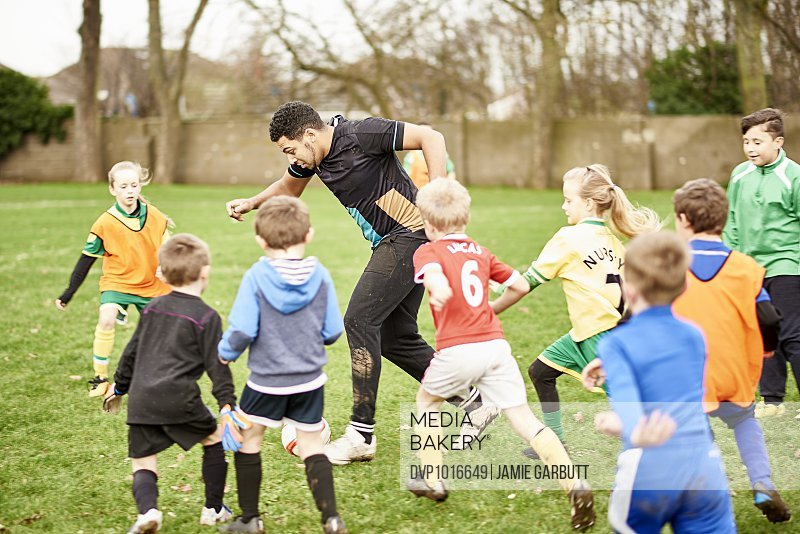 A parent playing football with children