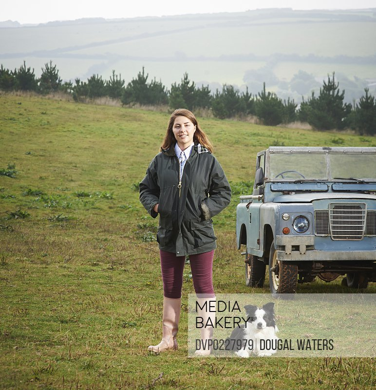 A female farmer stands with Border Collie dog and off road vehicle on her farm land