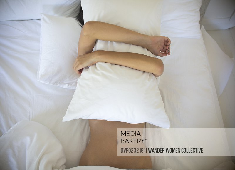 Woman in bed with pillow over face