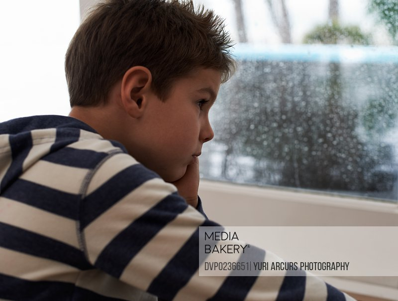 A young boy sitting by the window and looking bored while it rains outside