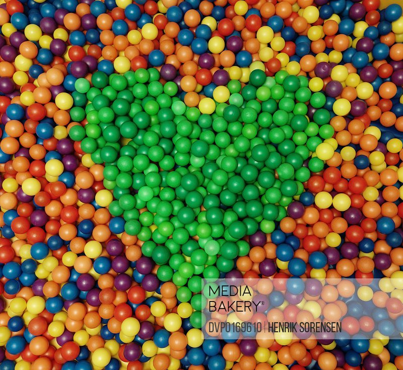 An abundance of balls of different colours with all the greens forming a heart in the middle
