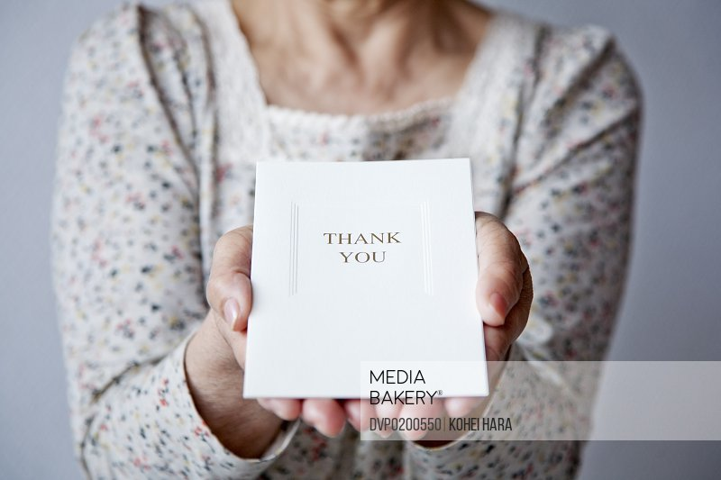 an elderly woman holding a card