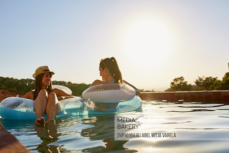 Friends in inflatable ring floating on pool