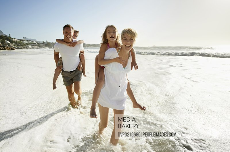 Smiling parents carrying their son and daughter down the beach