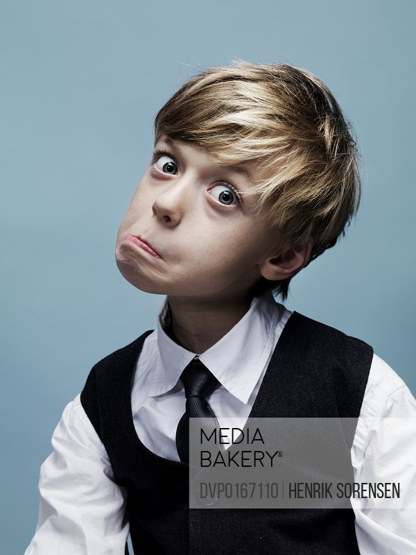 Head and shoulder portrait of young boy wearing a tie pulling a silly face