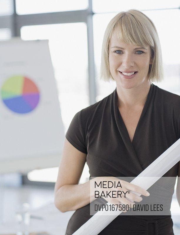 Businesswoman holding blueprints smiling