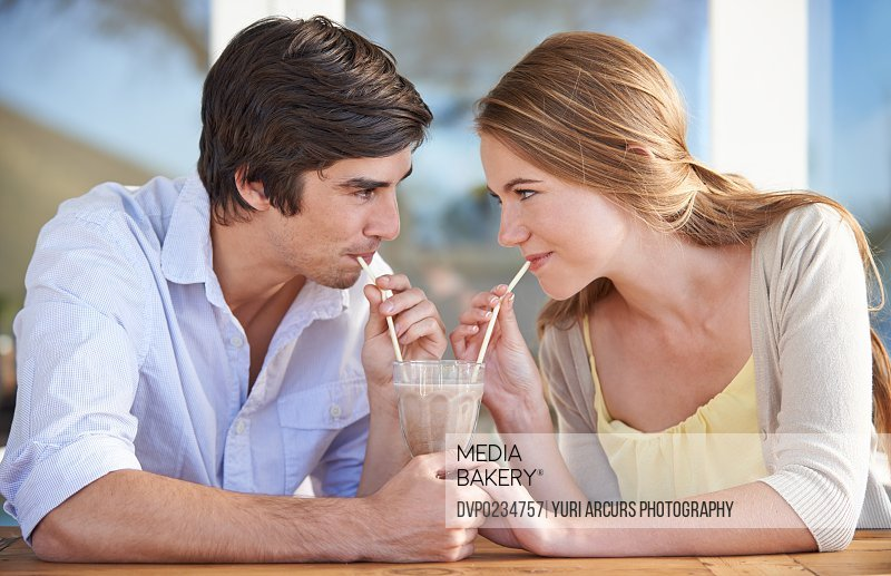 A young couple sharing a chocolate milkshake while on a date