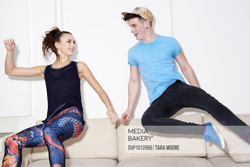 young man and woman jumping on sofa