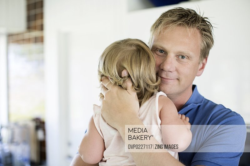 Father embracing female toddler 18-24 months portrait of father