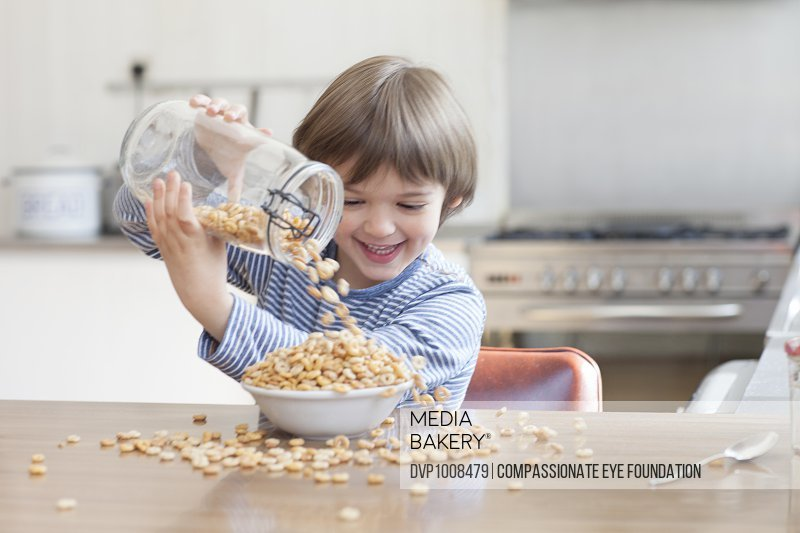 Boy pouring cereal into bowl in kitchen