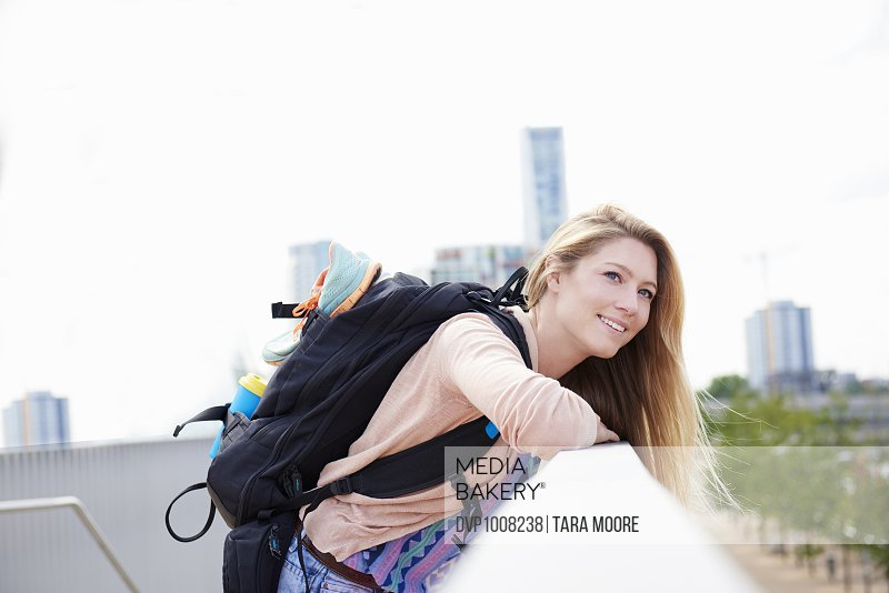 Young woman with sports bag enjoying view of city