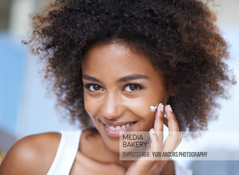 Portrait of an attractive young woman giving you a toothy smile while touching her skin