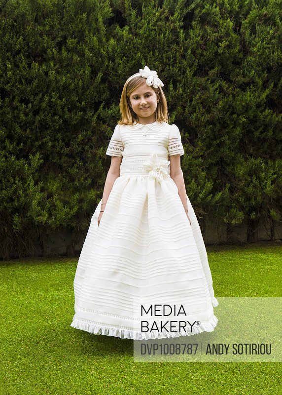Young girl wearing a communion dress apparently floating in the air
