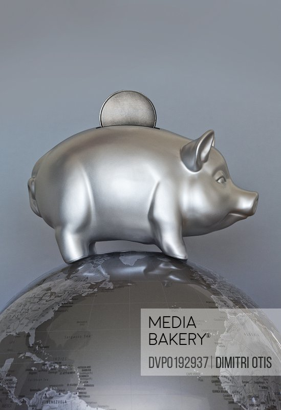 Silver piggy bank money box with coin on globe