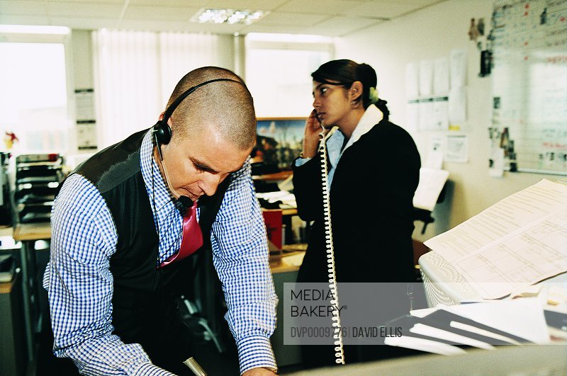 Young Businessman and Businesswoman Working in an Open Plan Office
