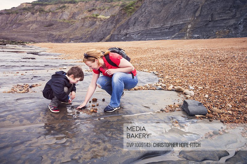 A mother clearing pebbles to one side on a  stretch of Dorset's jurassic coast while looking for fossils with her young son.