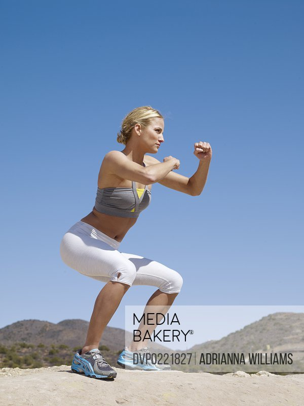 woman doing boxing workout move in desert
