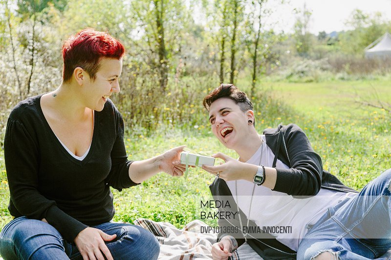 Lesbian woman receiving present sitting on grass