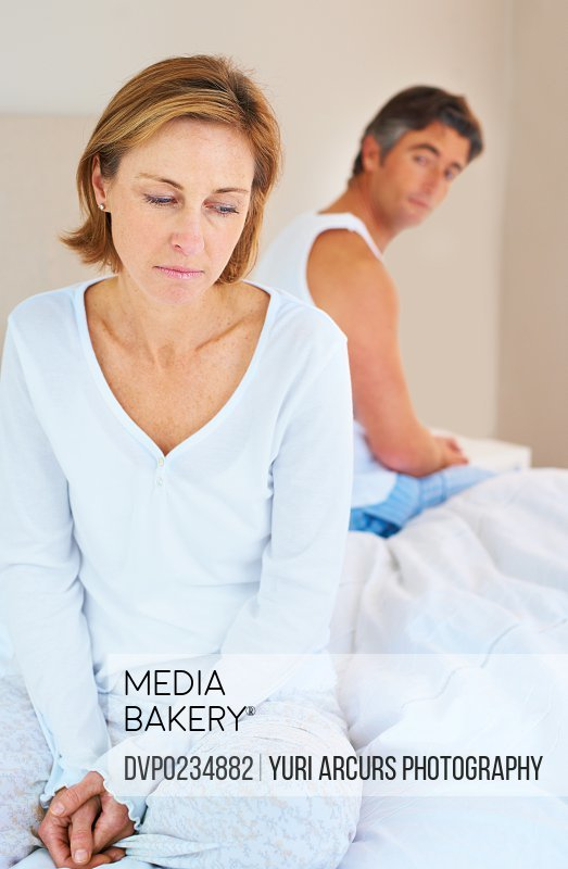 Mature woman feeling depressed while sitting on the bed with her husband