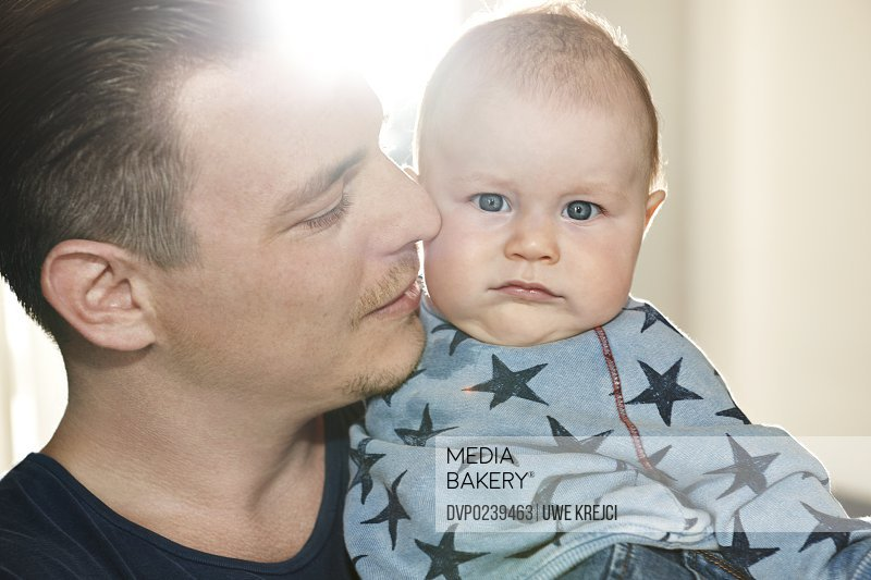 Father holding baby, close up