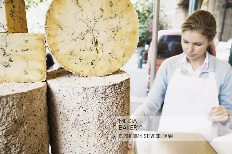 Woman working at cheese stall at market