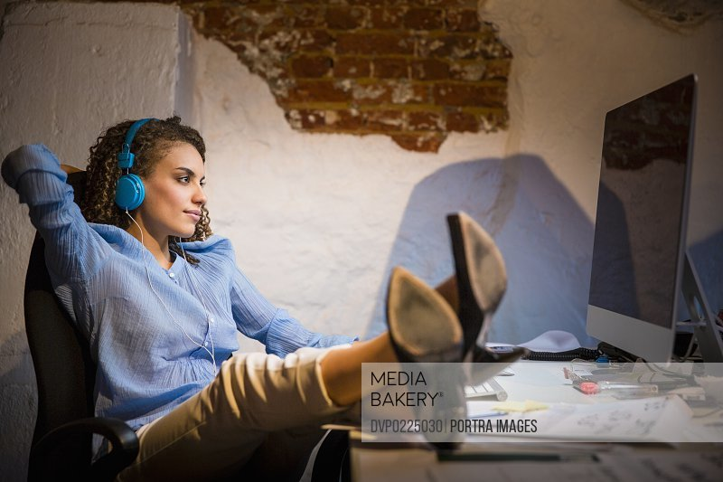 Relaxed businesswoman listening music in office