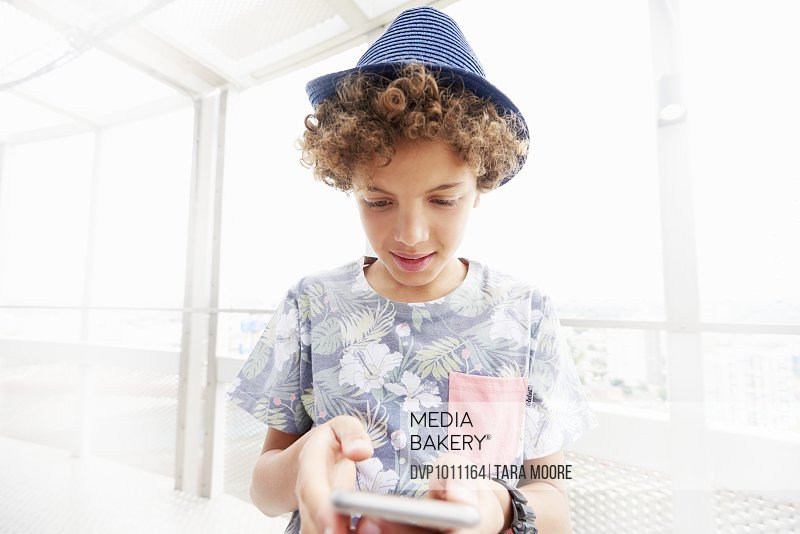 young boy playing with mobile