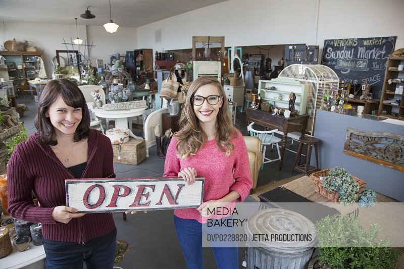 Two small business partners holding open sign