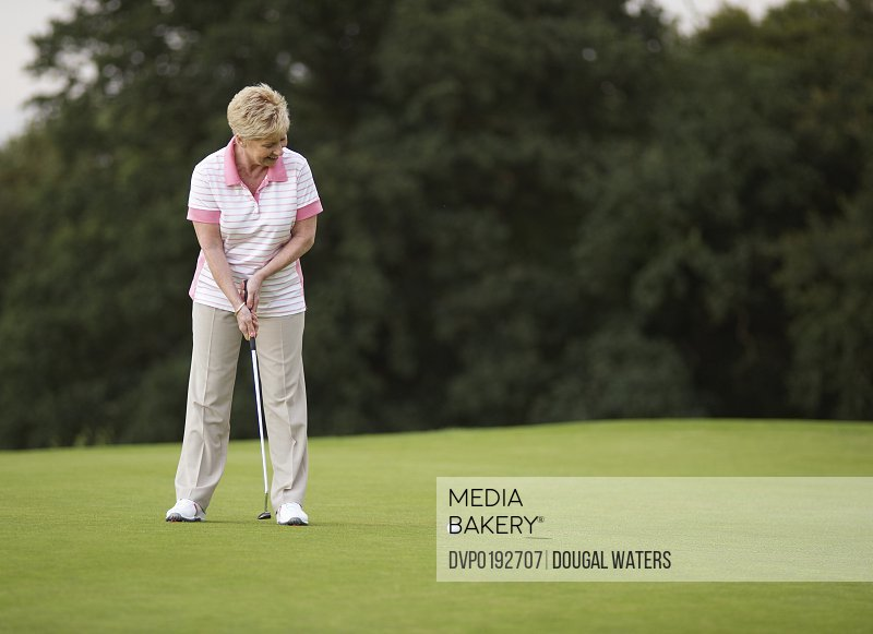 Female golfer putting ball towards hole.