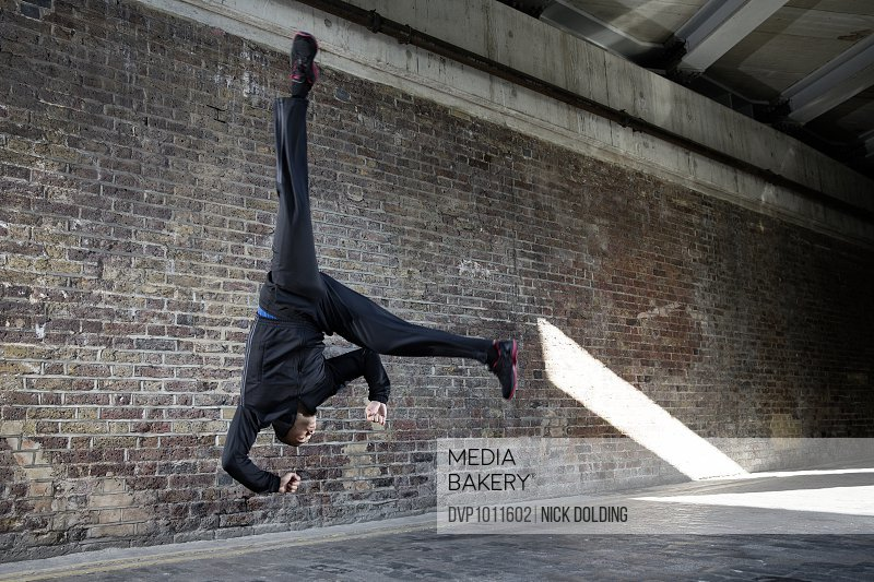 Man practicing Capoiera flip in urban setting