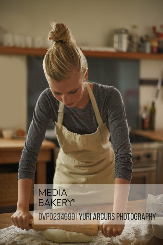 Shot of a young woman rolling dough with a rolling pin