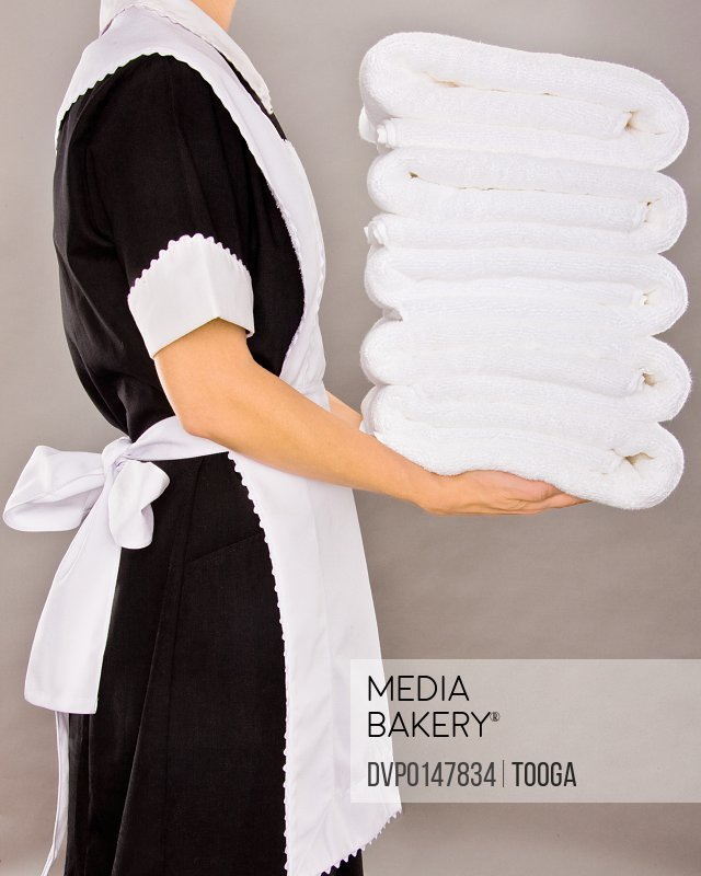 Maid holding white stack towels