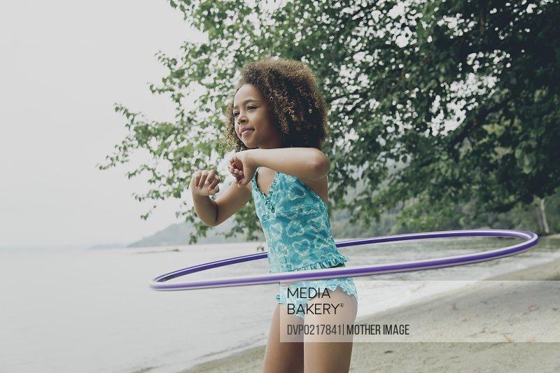 Young girl playing with hula hoop