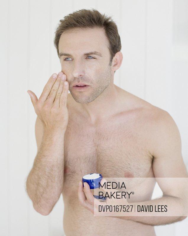 Bare-chested man applying moisturizer