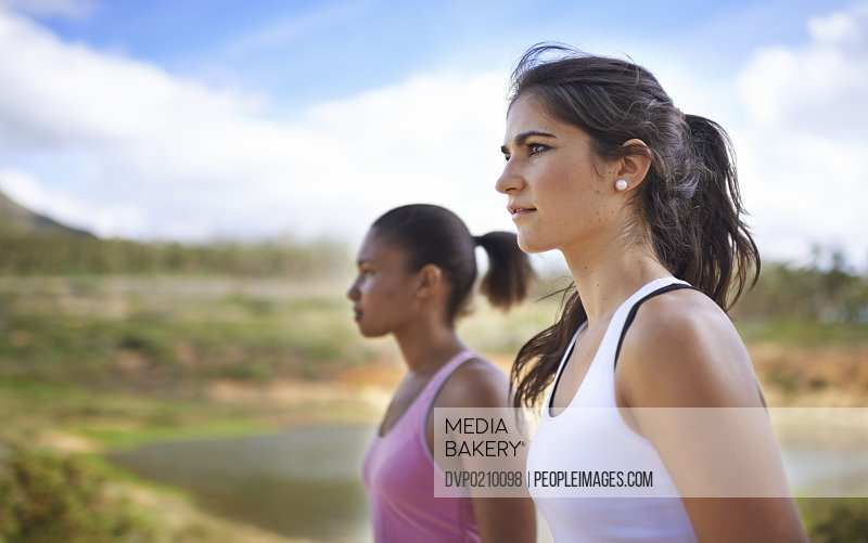 Two young women jogging outside - profile